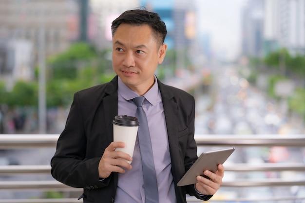 Uomo d'affari asiatico che sta e che tiene compressa digitale con gli edifici per uffici di affari nella città