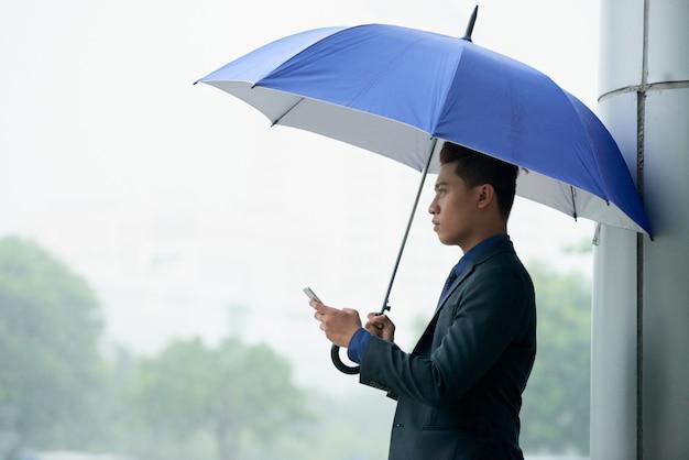 Uomo d'affari asiatico che sta in via con l'ombrello durante la pioggia e che per mezzo dello smartphone