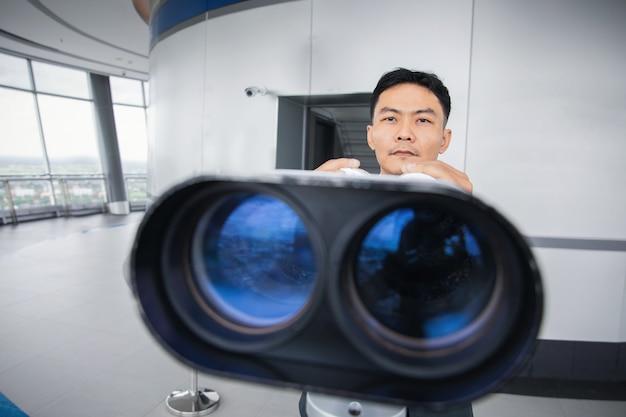 Uomo d'affari asiatico con il binocolo nella parte superiore dell'edificio