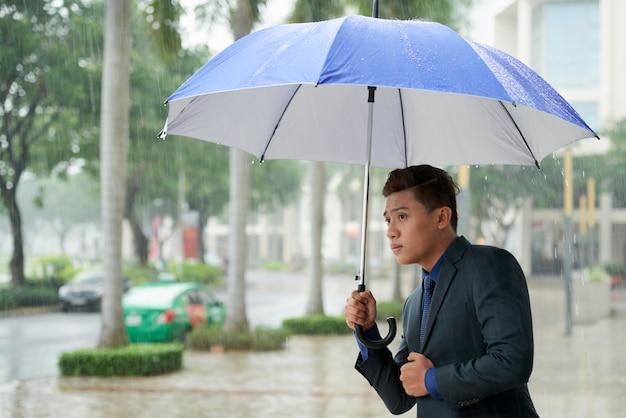 Uomo d'affari asiatico con l'ombrello che cerca taxi in via durante la pioggia