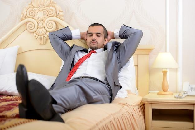 Uomo d'affari asiatico con la valigia che si trova su un letto.