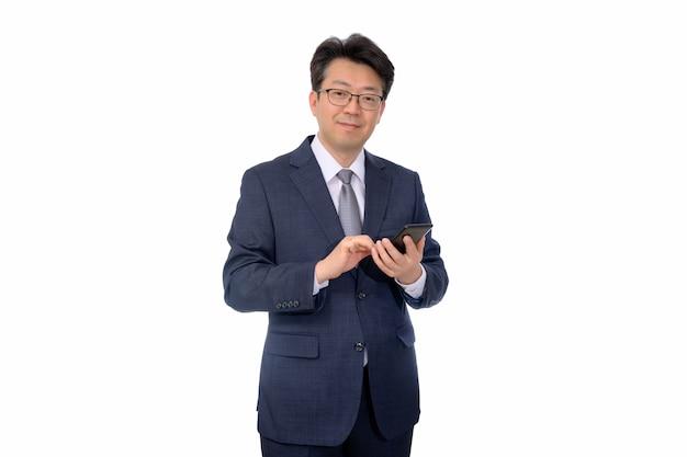 Uomo d'affari asiatico di medio evo che per mezzo di uno smartphone mobile su un fondo bianco.