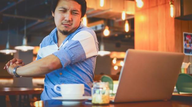 Uomo d'affari asiatico in vestito casuale che lavora con dolore al collo, mal di schiena o mal di testa