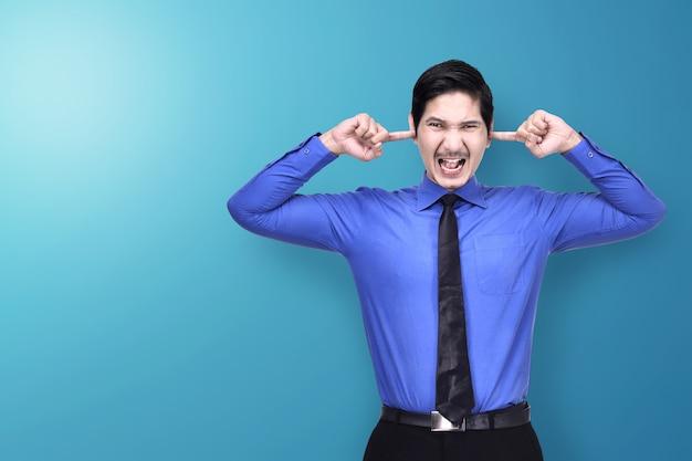 Uomo d'affari asiatico infelice che copre le sue orecchie di mano