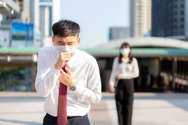 Uomo d'affari asiatico malato tossisce con la maschera con la donna d'affari in background per mantenere la distanza di protezione dai virus covid-19 e le persone che prendono le distanze sociali per il rischio di infezione