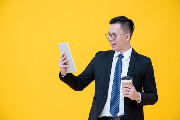 Uomo d'affari asiatico messo a fuoco che esamina il computer della compressa mentre bevendo caffè
