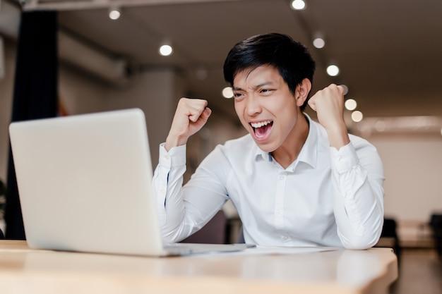 Uomo d'affari asiatico millenario in ufficio con il portatile soddisfatto della sua vittoria