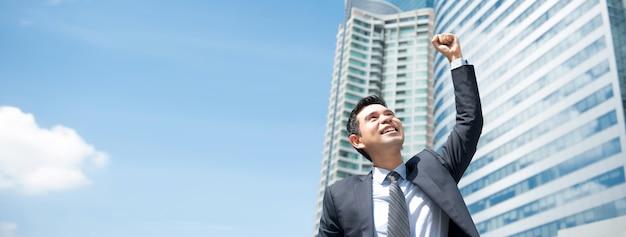Uomo d'affari asiatico potente che mostra vittoria, autorizzandosi, fuori dall'ufficio - bandiera panoramica