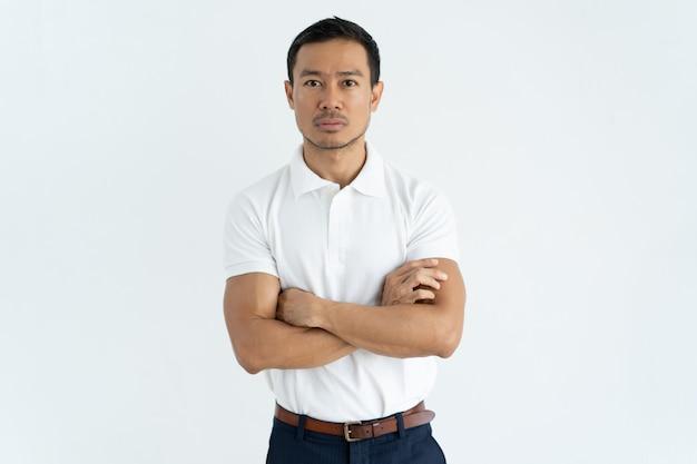 Uomo d'affari asiatico serio in maglietta bianca che esamina macchina fotografica