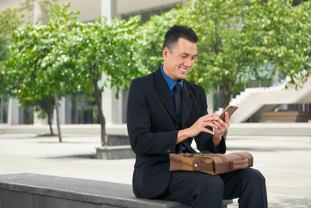 Uomo d'affari asiatico sorridente che per mezzo del telefono cellulare