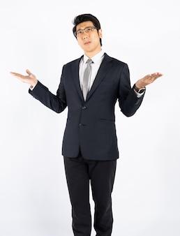 Uomo d'affari astuto confuso e sorpreso contro la parete bianca