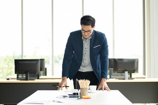 Uomo d'affari astuto e bello che sta nella sala riunioni in ufficio