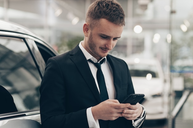 Uomo d'affari attraente che compra nuova automobile al concessionario