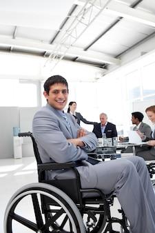 Uomo d'affari attraente che si siede in una sedia a rotelle con le braccia piegate
