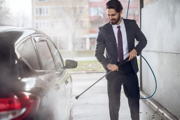 Uomo d'affari barbuto alla moda soddisfatto felice bello nel vestito che pulisce l'automobile con una pistola a acqua nella stazione di lavaggio di self service manuale.