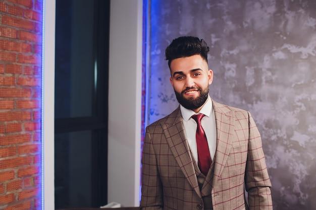 Uomo d'affari barbuto bello in vestito classico.