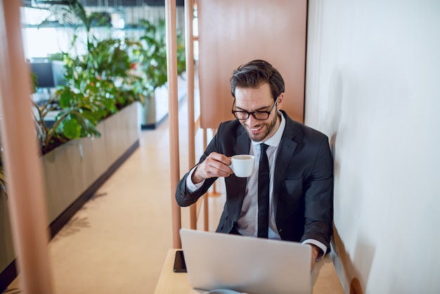 Uomo d'affari barbuto caucasico bello entusiasta in vestito e con gli occhiali seduto al tavolo, bere caffè e rapporto di finitura. interno dell'azienda.