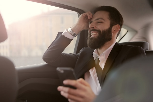 Uomo d'affari barbuto che viaggia in un'automobile