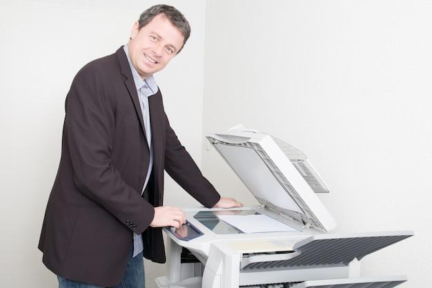 Uomo d'affari bello al posto di lavoro con la copiatrice della fotocopiatrice all'ufficio