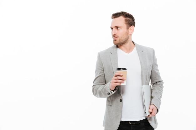 Uomo d'affari bello che beve caffè.