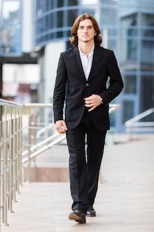 Uomo d'affari bello che cammina alla macchina fotografica