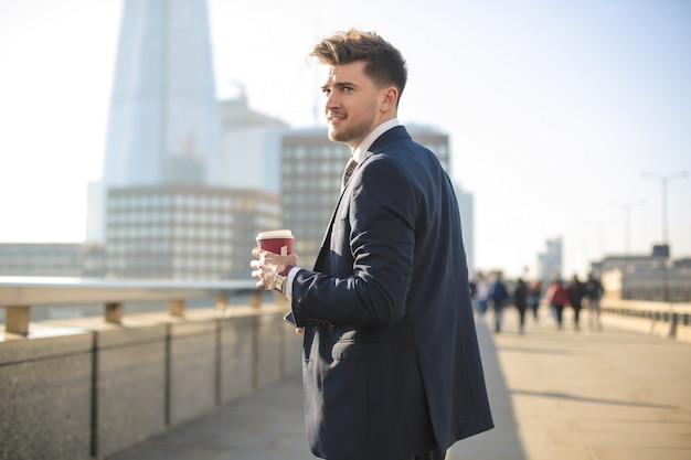 Uomo d'affari bello che cammina sul ponte di londra