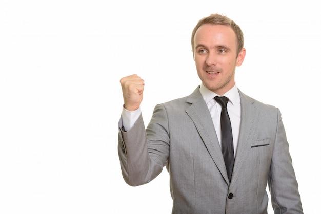 Uomo d'affari bello che dà discorso isolato contro la parete bianca