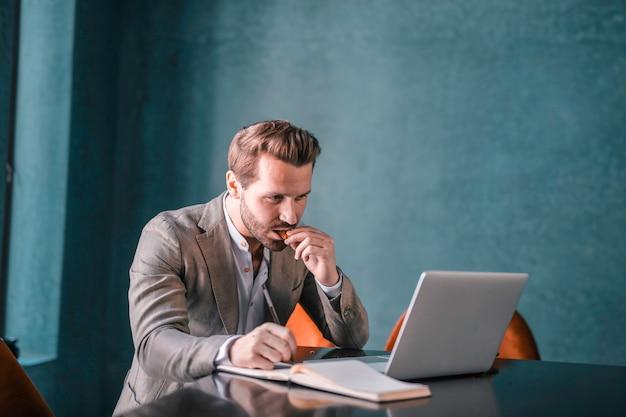 Uomo d'affari bello che lavora ad un computer portatile