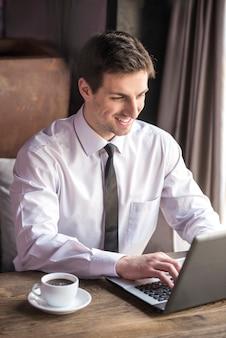 Uomo d'affari bello che lavora al computer portatile con la tazza di caffè.