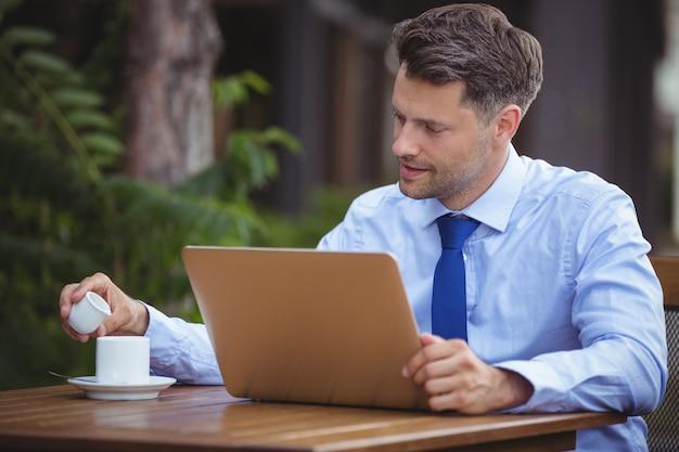 Uomo d'affari bello che mangia tè mentre per mezzo del computer portatile