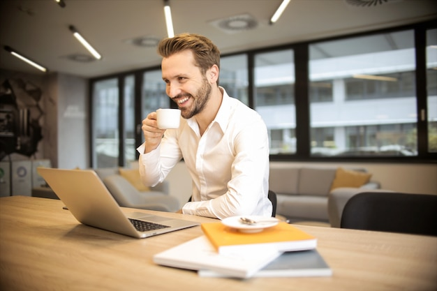 Uomo d'affari bello che mangia un caffè