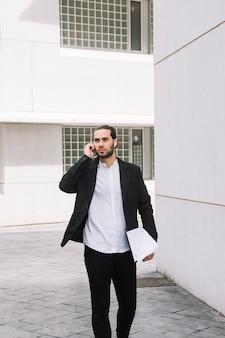 Uomo d'affari bello che parla sui documenti della tenuta del telefono cellulare nelle mani