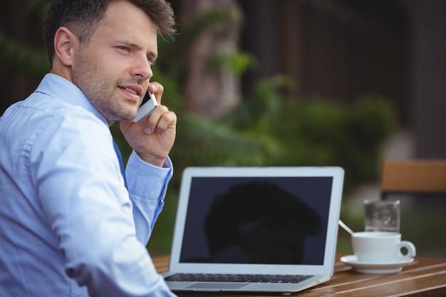Uomo d'affari bello che parla sul telefono cellulare mentre per mezzo del computer portatile