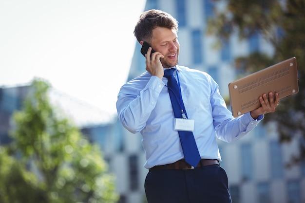 Uomo d'affari bello che parla sul telefono cellulare