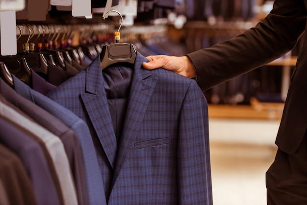 Uomo d'affari bello che sceglie vestito classico.