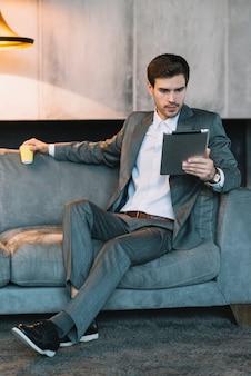 Uomo d'affari bello che si siede sul sofà che tiene tazza eliminabile che esamina compressa digitale