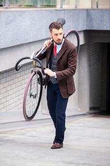 Uomo d'affari bello che trasporta la sua bicicletta sulle strade della città. il concetto dello stile di vita moderno dei giovani uomini