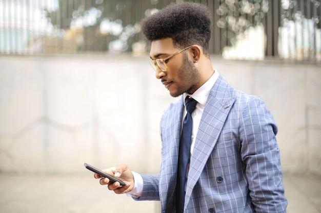 Uomo d'affari bello che usando le cuffie per chiamare con il suo telefono