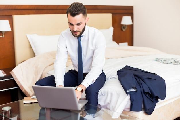 Uomo d'affari bello che utilizza computer portatile nella camera di albergo
