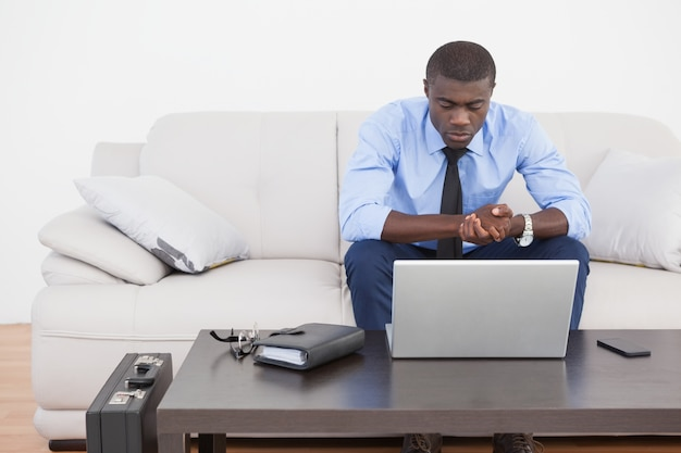 Uomo d'affari bello che utilizza computer portatile sul sofà