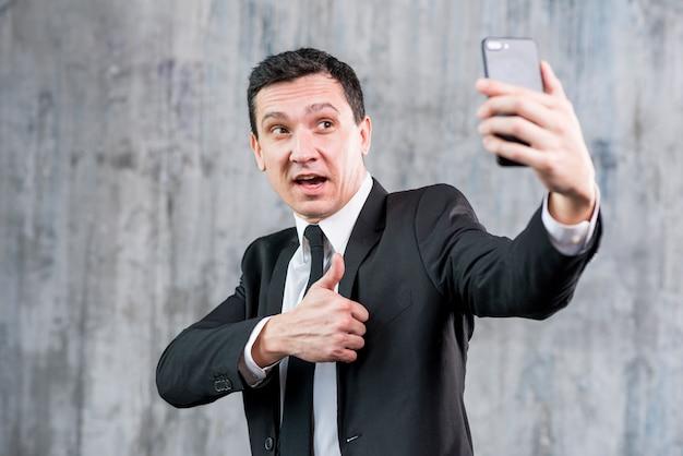 Uomo d'affari bello con il pollice in su prendendo selfie