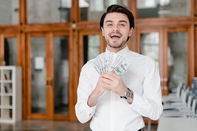 Uomo d'affari bello con soldi nell'ufficio