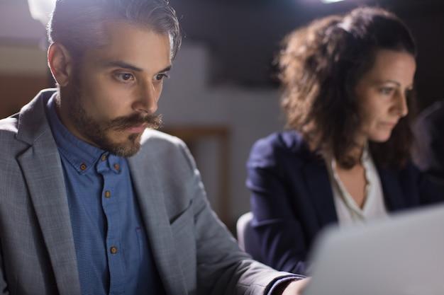 Uomo d'affari bello concentrato che esamina computer portatile