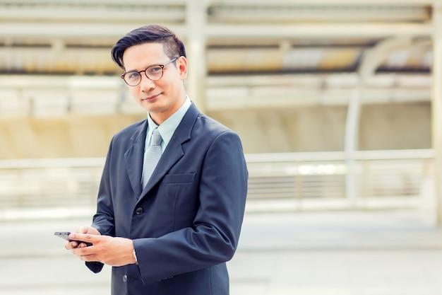 Uomo d'affari bello del giovane asia con il suo smartphone che sta sul passaggio pedonale della città moderna.