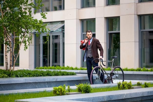 Uomo d'affari bello e la sua bicicletta