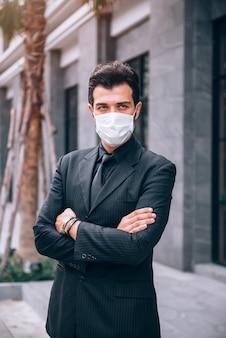 Uomo d'affari bello in piedi nel quartiere degli affari e fiducioso nel nuovo progetto di business tra situazione di scoppio coronavirus covid-19. sanità e concetto di business
