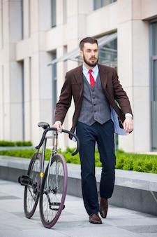 Uomo d'affari bello in una giacca e cravatta rossa e la sua bicicletta sulle strade della città. il concetto dello stile di vita moderno dei giovani uomini