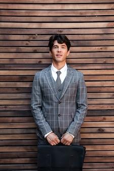Uomo d'affari bello in vestito che sta con la cartella contro la parete di legno