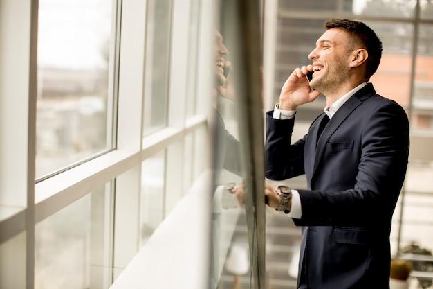 Uomo d'affari bello in vestito classico che parla sul telefono cellulare