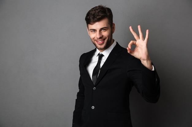Uomo d'affari bello in vestito nero che mostra gesto giusto,